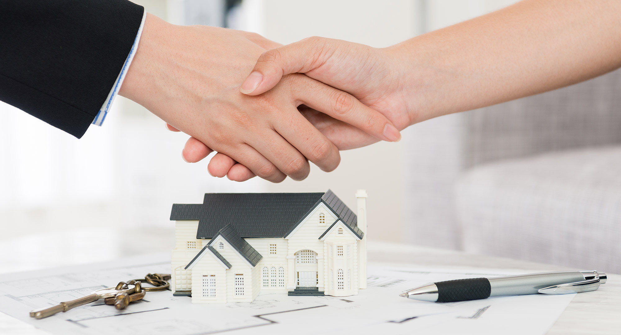 A real estate agent and home buyer shake hands.