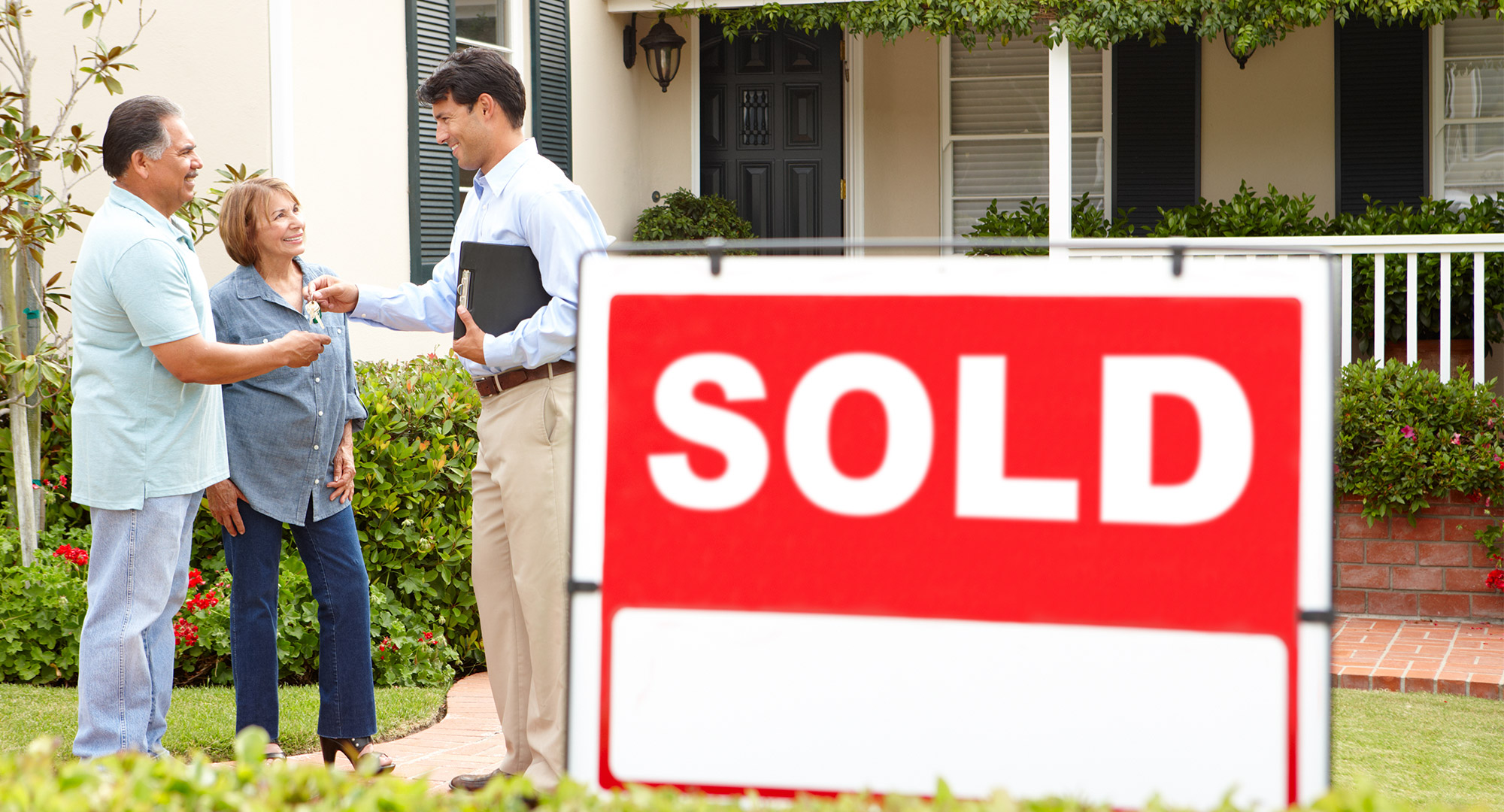 A happy senior Hispanic couple buying new home.